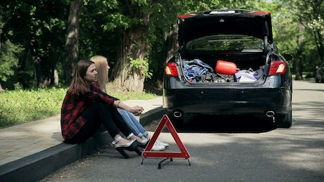 Young women sit on curb after auto accident
