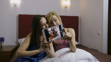 Young women taking a photo in bed
