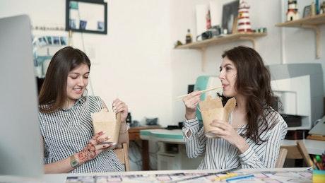 Young women talk over lunch break in modern office