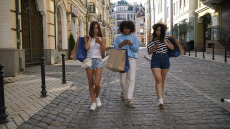 Young women walking with their phones
